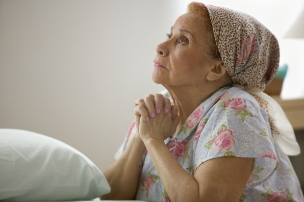 Elderly woman praying before bed