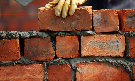 man building a brick wall