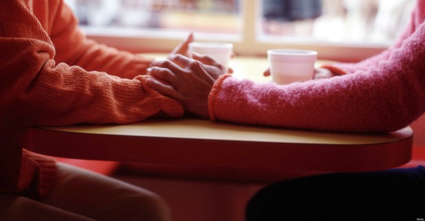 Two women at cafe table holding hands
