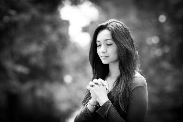 Woman hands praying with a blible in his legs Outdoors black and white