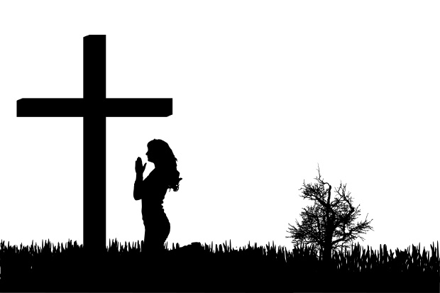 Vector silhouette of a woman who is praying at the cross.