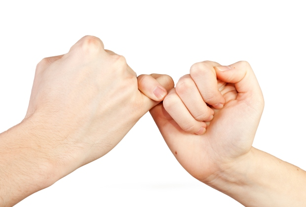 Man and woman making a pinky promise. Hands isolated on white background.