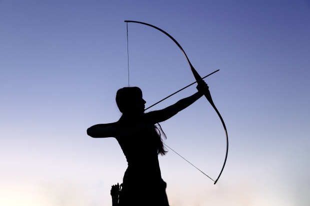 Female ginger hair archer shooting targets with her bow and arrow. Concentration, target, success concept