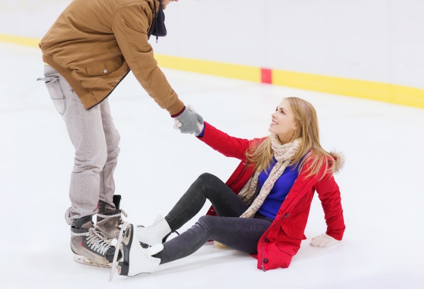 man helping women to rise up on skating rink